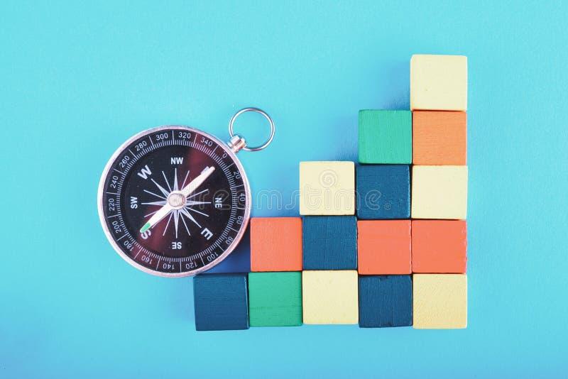 Compasso e cubo de madeira colorido no fundo azul imagem de stock