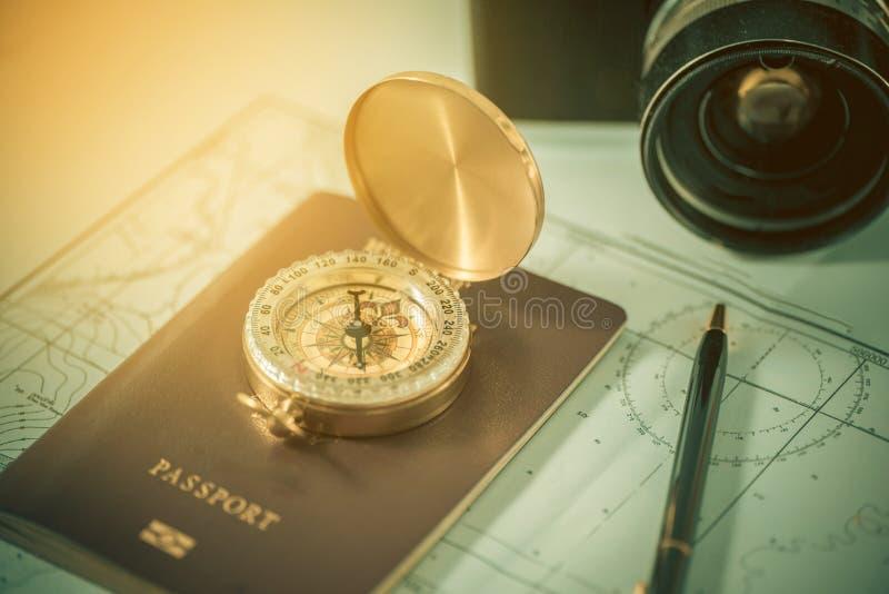 Compasso em um passaporte dos E.U. e mapa com a câmera velha borrada fotografia de stock