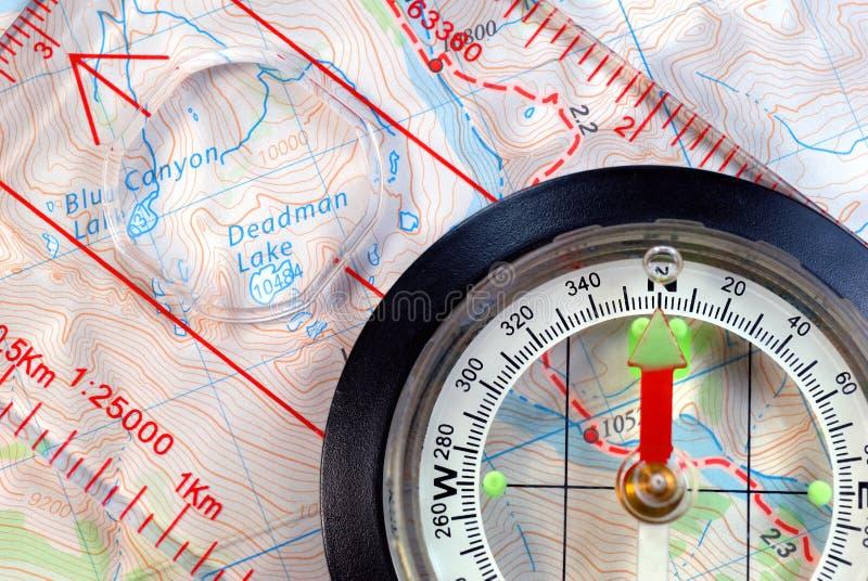 Compasso navegacional no mapa topográfico fotografia de stock