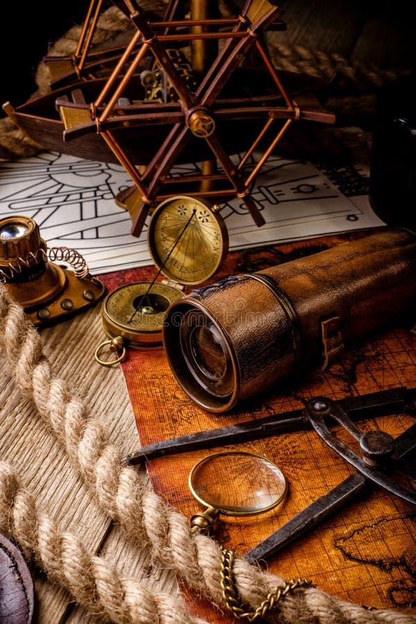 Compasso retro e telescópio pequeno do vintage velho no mapa do mundo antigo fotografia de stock