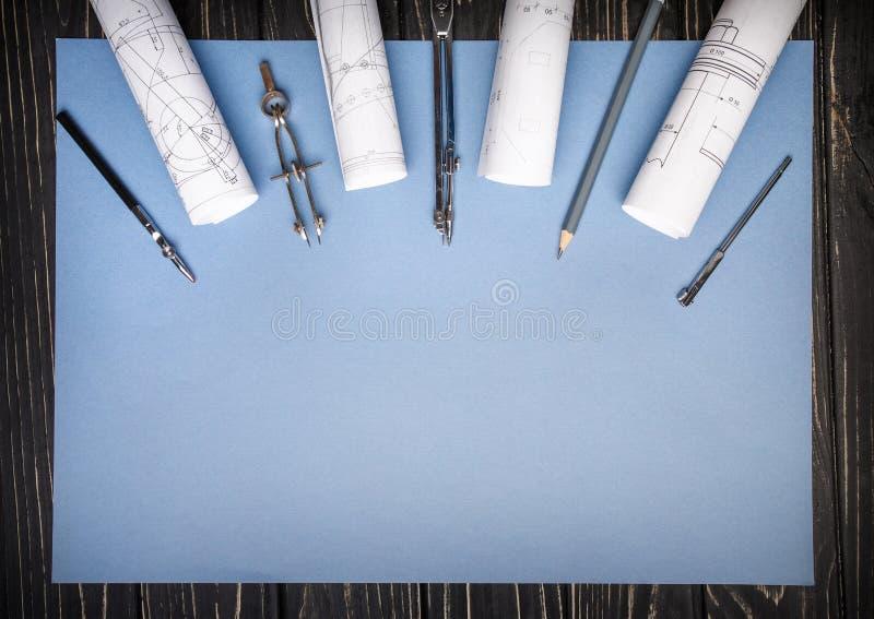 Compassos, réguas do desenho e um lápis em um fundo azul fotografia de stock