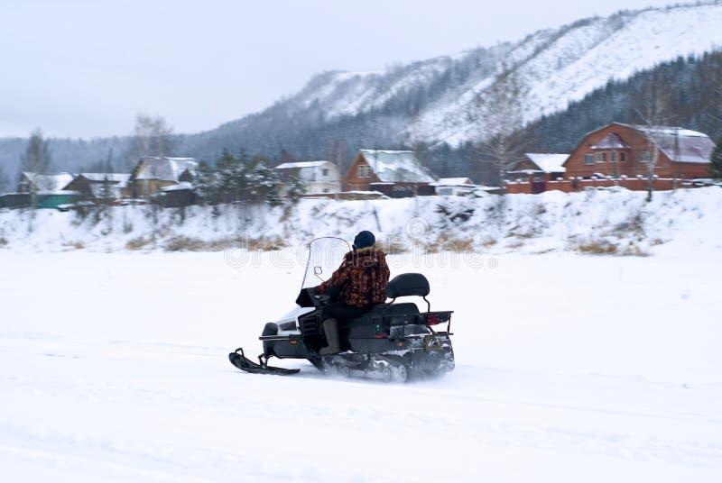 Compatriote sur un motoneige dans un paysage neigeux d'hiver photo libre de droits