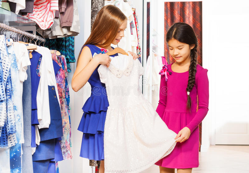Compera delle ragazze ed uno di loro che tengono vestito bianco fotografia stock libera da diritti