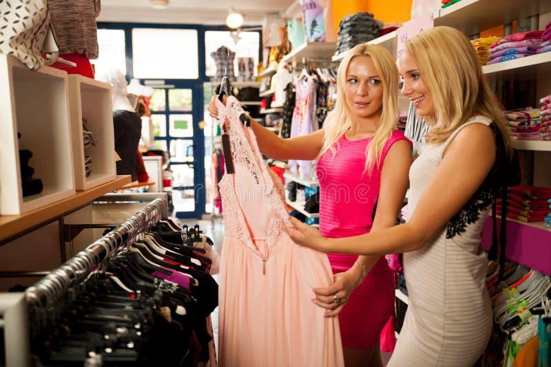 Comperando nel deposito dei vestiti - due donne sveglie nel negozio dell'abbigliamento selezionano fotografia stock libera da diritti