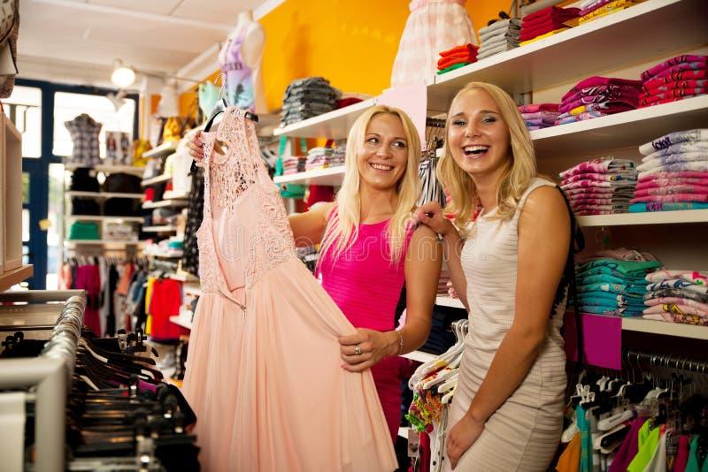 Comperando nel deposito dei vestiti - due donne sveglie nel negozio dell'abbigliamento selezionano fotografia stock