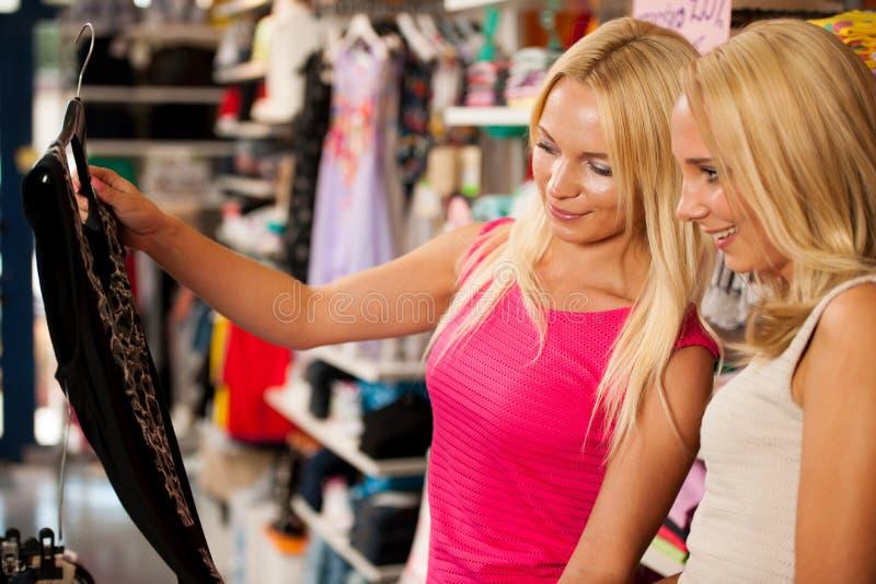 Comperando nel deposito dei vestiti - due donne sveglie nel negozio dell'abbigliamento selezionano immagini stock