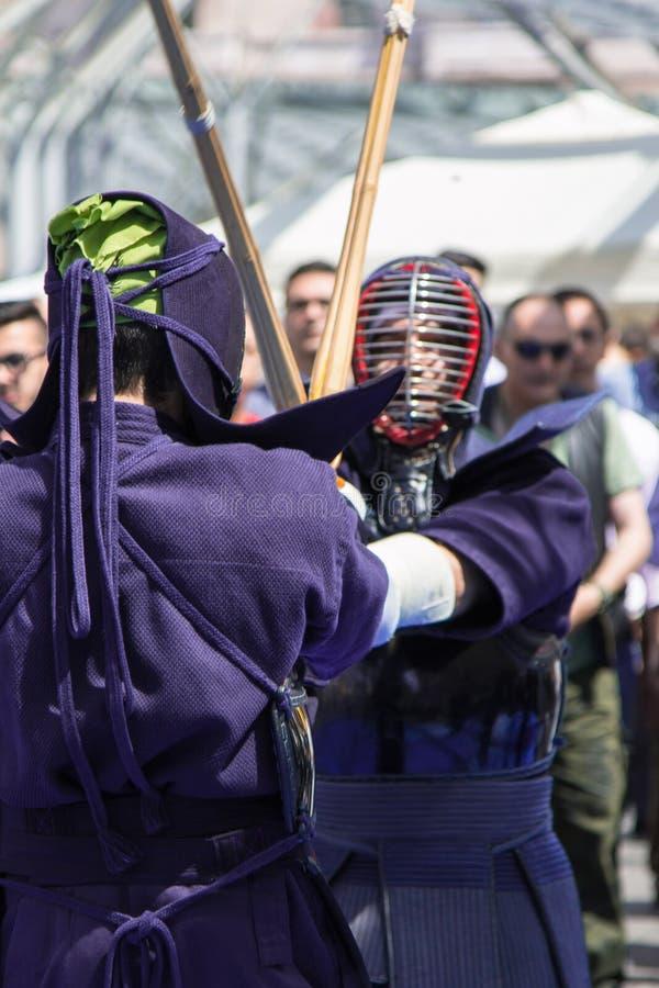 Competencia de dos combatientes del kendo con la espada de bambú y tradicional imagen de archivo