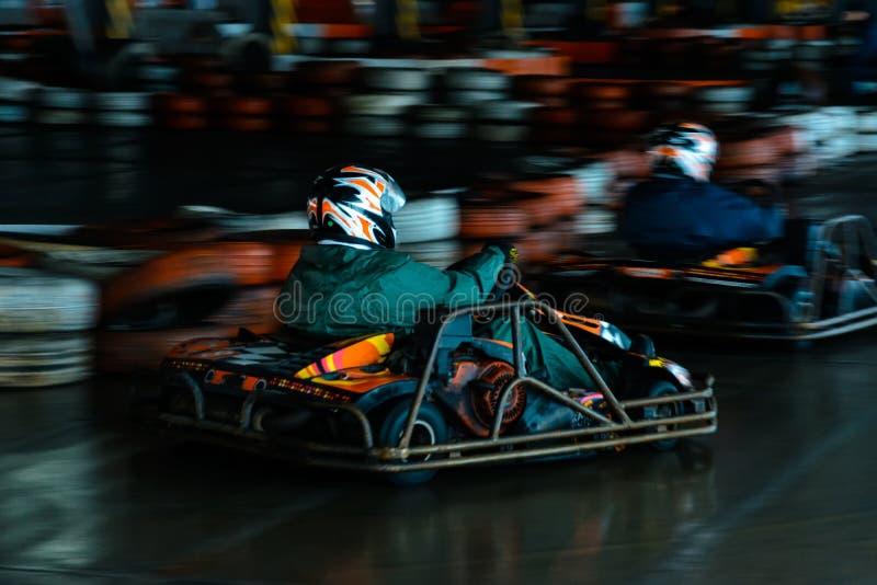 Competencia karting din?mica a la velocidad con el movimiento borroso en un hip?dromo equipado fotos de archivo