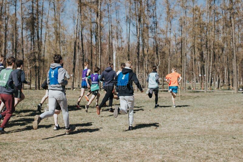 Competencia menor Los muchachos jovenes corren a través del bosque, participan en la competencia fotografía de archivo