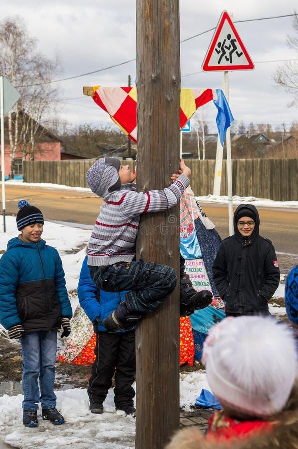 Competencia nacional rusa subiendo un polo de madera en conmemoración de finales del invierno en la región de Kaluga el 13 de mar foto de archivo libre de regalías