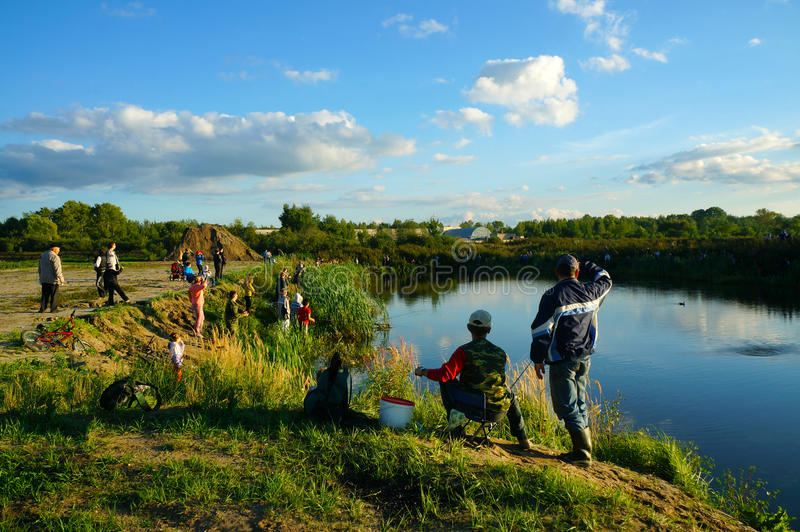 Competencias de deportes en la pesca en la cogida de una carpa y de un esturión, pescadores en el lago imagenes de archivo