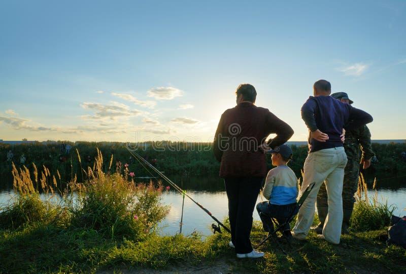 Competencias de deportes en la pesca en la cogida de una carpa y de un esturión, pescadores en el lago foto de archivo libre de regalías