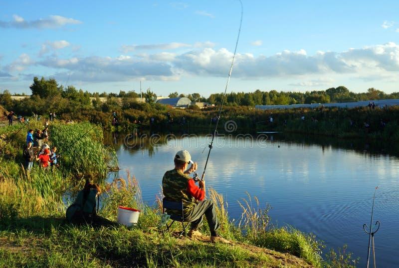 Competencias de deportes en la pesca en la cogida de una carpa y de un esturión, pescadores en el lago imágenes de archivo libres de regalías