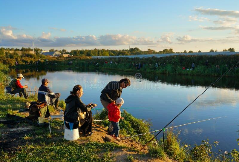 Competencias de deportes en la pesca en la cogida de una carpa y de un esturión, pescadores en el lago foto de archivo
