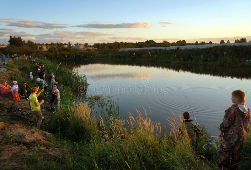 Competencias de deportes en la pesca en la cogida de una carpa y de un esturión, pescadores en el lago imagen de archivo libre de regalías