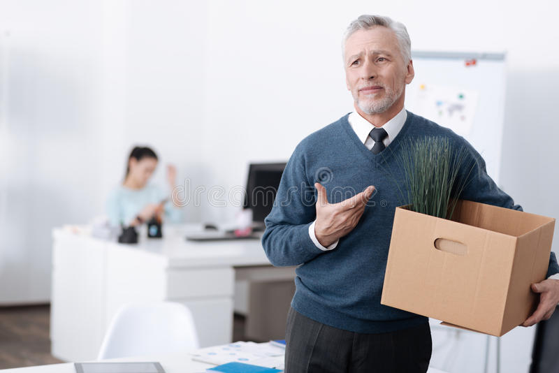 Competent bearded man asking for help. I did not expected this. Man in years wrinkling his forehead looking aside while standing in office stock photo