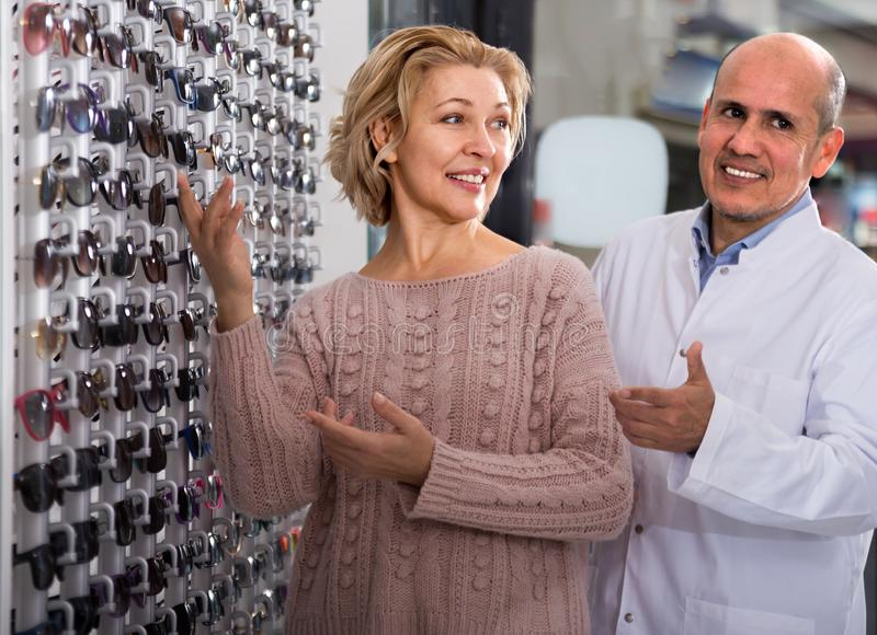 man optician client counseling Mature Blonde near the display Sunglasses royalty free stock image