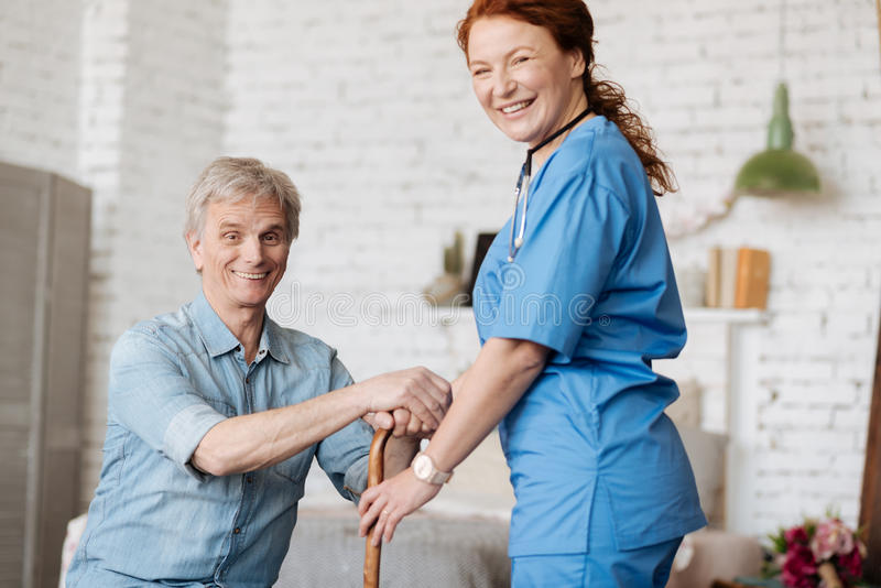 Competent private nurse conducting treatment procedures at home stock photos