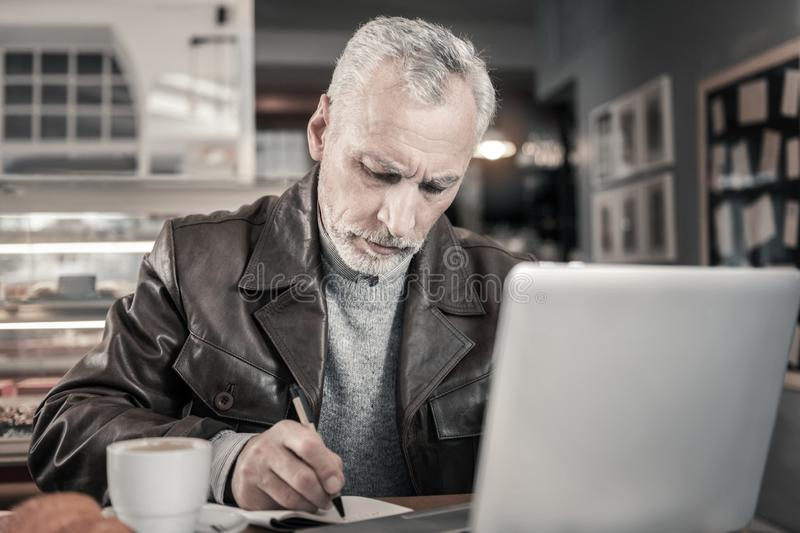 Concentrated gray-haired male making notes in copybook. Competent worker. Serious male person wrinkling forehead while thinking about result stock image