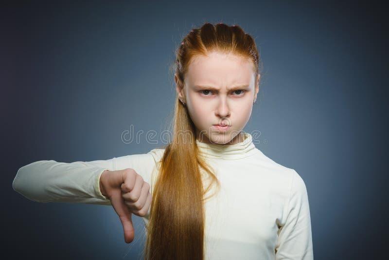 Competição falhada a menina que mostra o polegar gesticula para baixo o fundo cinzento isolado foto de stock royalty free