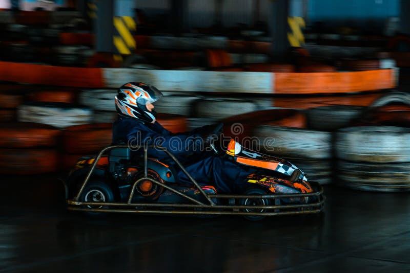 Competição karting dinâmica na velocidade com movimento obscuro em uma pista de corridas equipada foto de stock royalty free