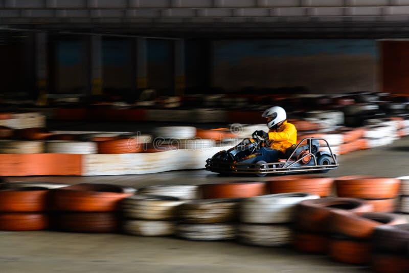 Competição karting dinâmica na velocidade com movimento obscuro em uma pista de corridas equipada fotos de stock