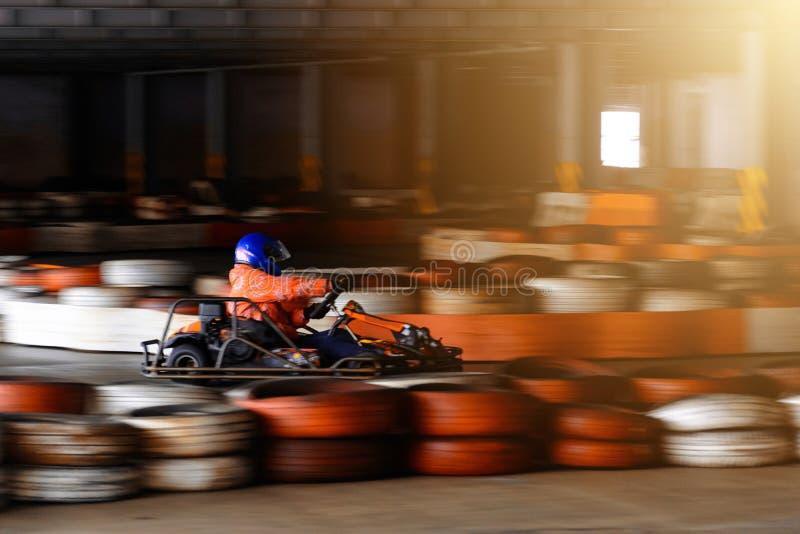 Competição karting dinâmica na velocidade com movimento obscuro em uma pista de corridas equipada imagens de stock