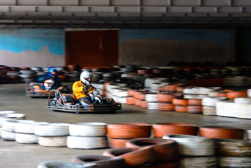 Competi??o karting din?mica na velocidade com movimento obscuro em uma pista de corridas equipada imagem de stock