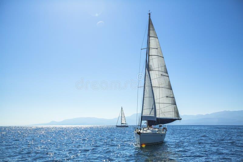 Competidor del barco de la regata de la navegación en tiempo soleado claro foto de archivo