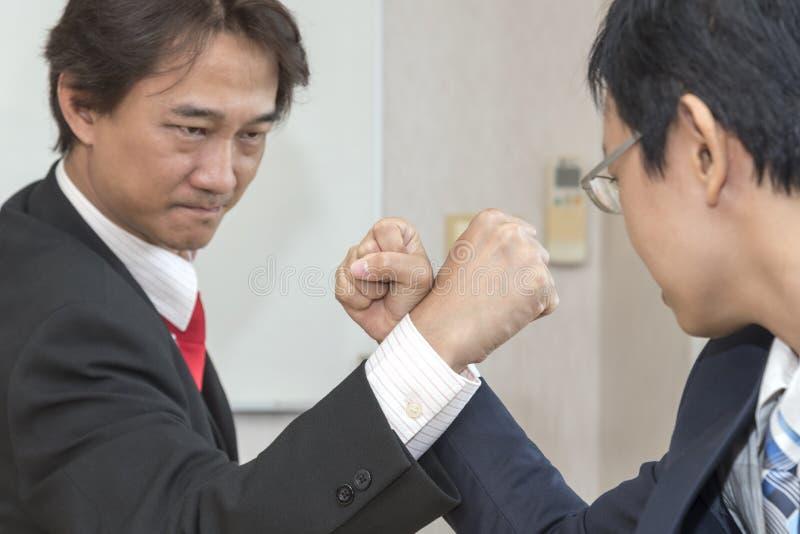 Competing In Arm för två affärsman brottning arkivbilder