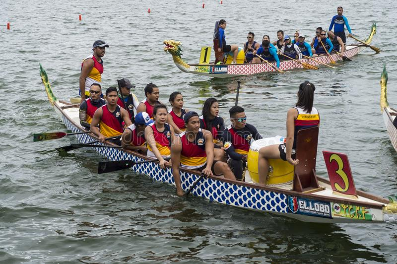 Competing teams of people embark on Sports Native Row Dragon head Boats during Dragon Cup Competition. San Pablo City, Laguna, Philippines - January 9, 2016 stock images