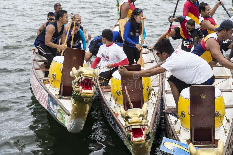 Competing teams of people embark on Sports Native Row Dragon head Boats during Dragon Cup Competition. San Pablo City, Laguna, Philippines - January 9, 2016 royalty free stock images