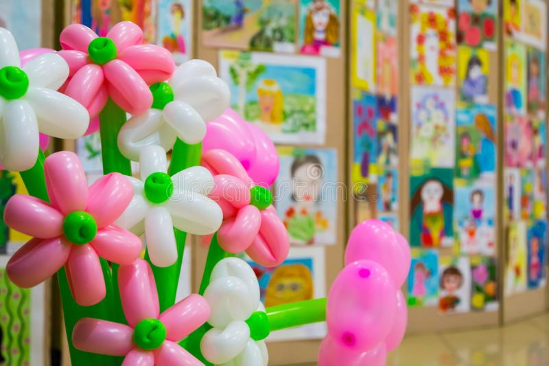 Competition of children`s drawings. Exhibition of children`s art. Colorful balloons in the foreground. Defocused background.  stock photo