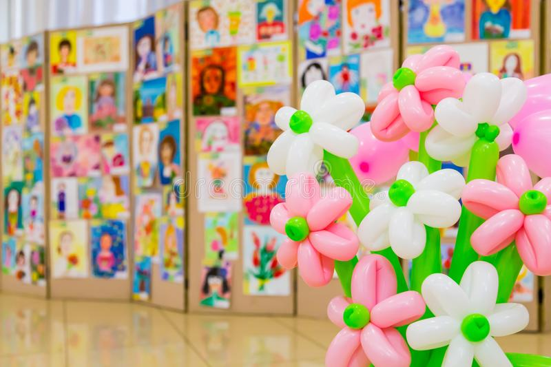 Competition of children`s drawings. Exhibition of children`s art. Colorful balloons in the foreground. Defocused background.  royalty free stock photos