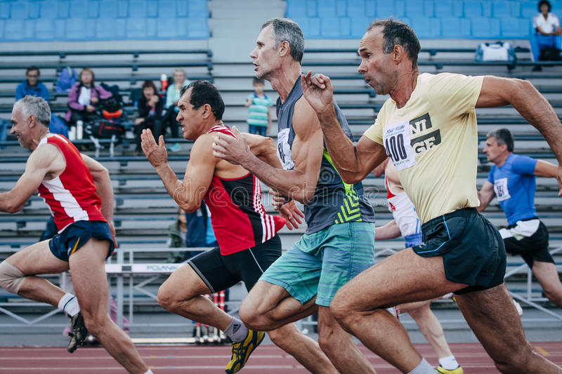 Competition old men athletes at the distance of 100 meters. Chelyabinsk, Russia - August 28, 2015: competition old men athletes at the distance of 100 meters royalty free stock photography