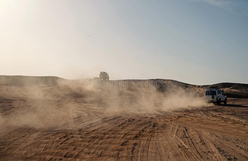 Competition racing challenge desert. Car overcome sand dunes obstacles. Car drives offroad with clouds of dust. Offroad. Vehicle racing obstacles in wilderness royalty free stock images