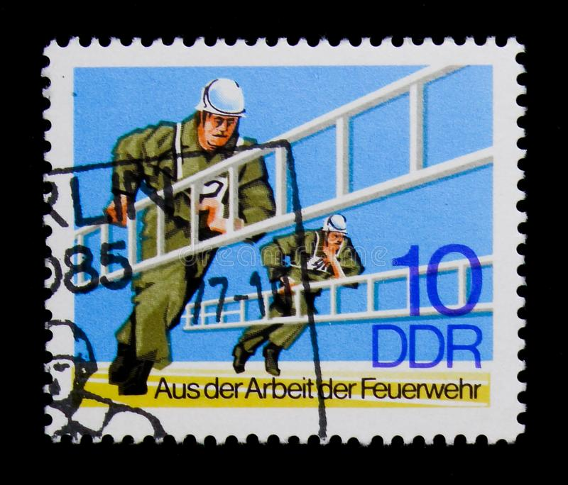 Competition with steep path conductors, From The Work Of The Fire Brigade serie, circa 1977. MOSCOW, RUSSIA - NOVEMBER 23, 2017: A stamp printed in Germany DDR royalty free stock photo