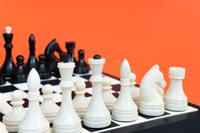 Competition or victory or strategy concept. Chess figures on orange background top view copy space. Competition or victory or strategy concept. Chess figures on royalty free stock images