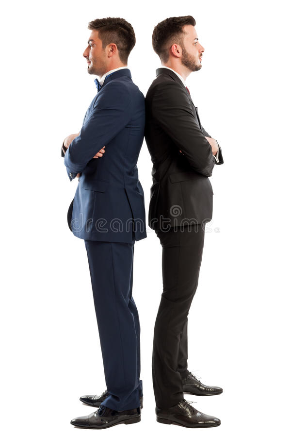 Competitive business men standing back to back stock images