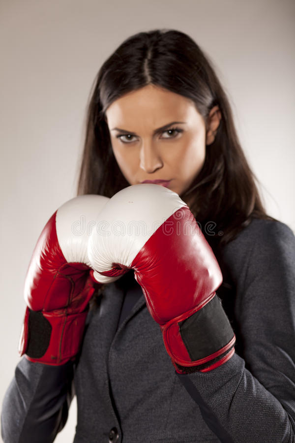 Competitive business woman. Angry business woman with boxing gloves on grey background royalty free stock photography