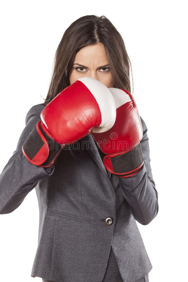 Competitive business woman. Angry business woman with boxing gloves on white background stock image