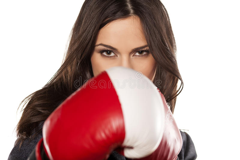 Competitive business woman. Angry business woman with boxing gloves on white background royalty free stock photography