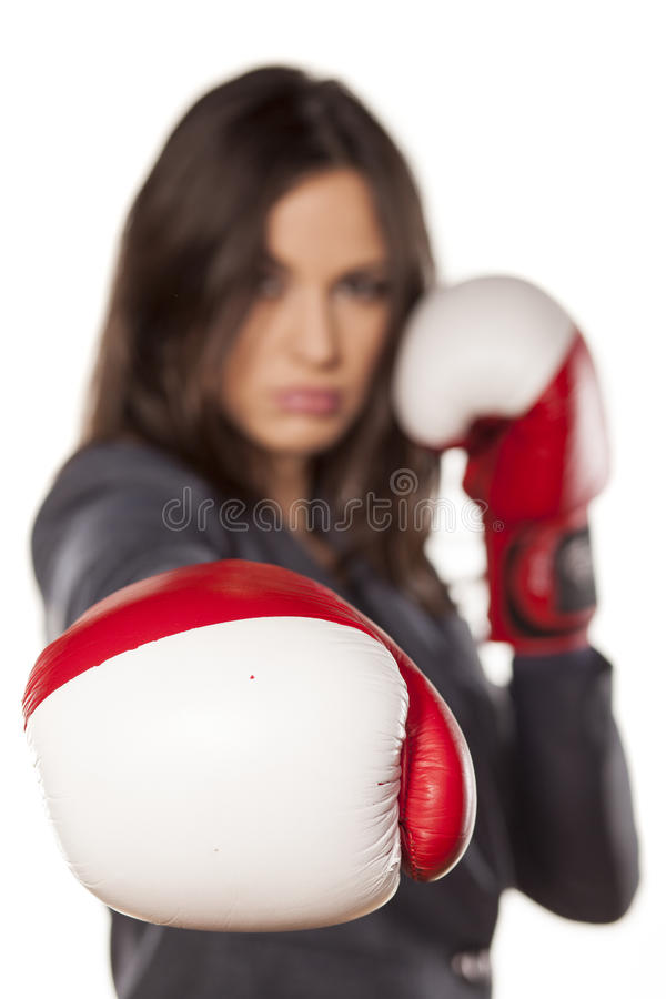 Competitive business woman. Angry business woman with boxing gloves on white background royalty free stock image