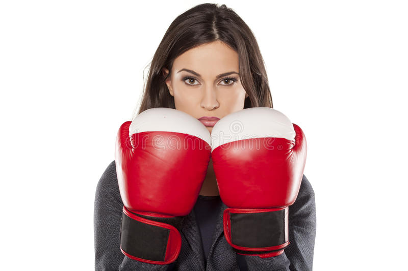 Competitive business woman. Serious business woman with boxing gloves on white background royalty free stock images