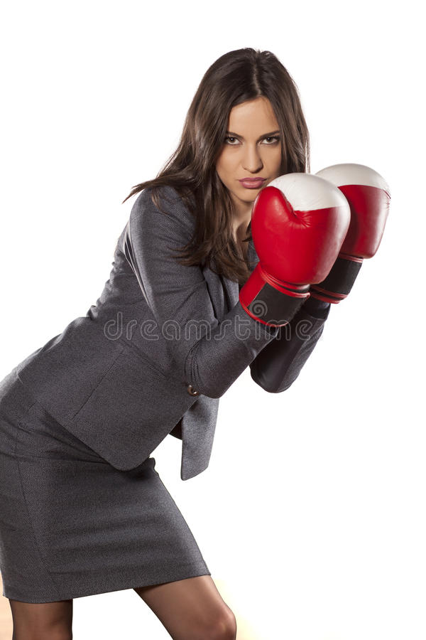 Competitive business woman. Serious business woman with boxing gloves on white background royalty free stock photos