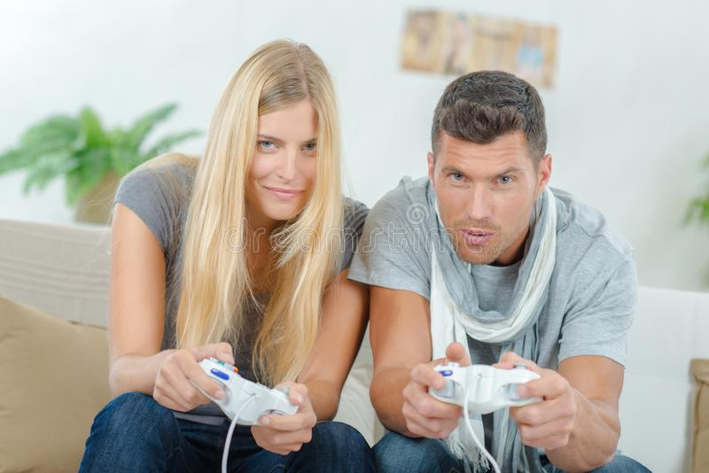 Competitive couple playing video games. Accomplice royalty free stock photos