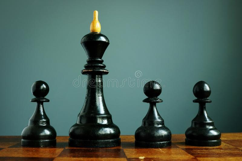Competitive edge or business advantage in recruitment. Pawns and chess king. Competitive edge or business advantage in recruitment. Black Pawns and chess king stock image