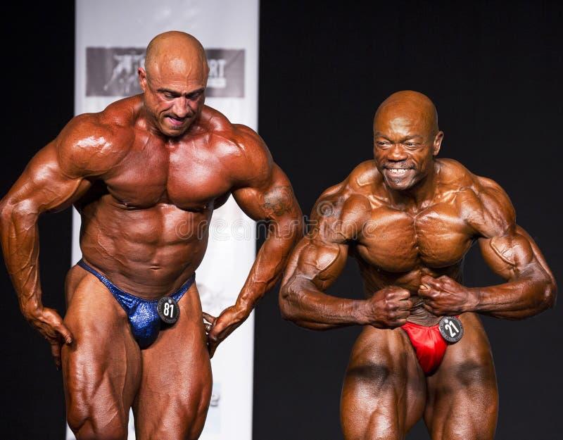 Competitive Middle-Aged Bodybuilders Flexing During Posedown. Muscular giants Robert Castarelli (Heavyweight Class winner) and Sheldon Hall (Lightweight Class stock photo