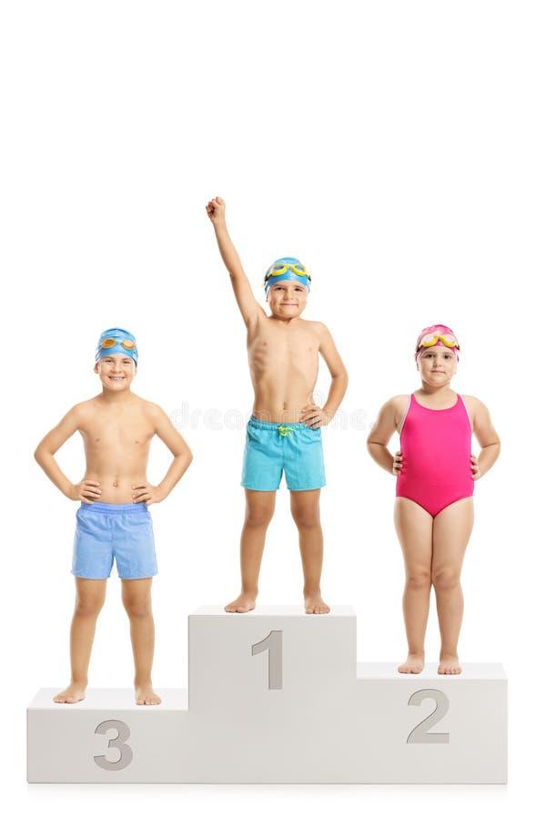 Competiton de la natación del ` s de los niños, tres niños en un PED del ` s del ganador imagenes de archivo