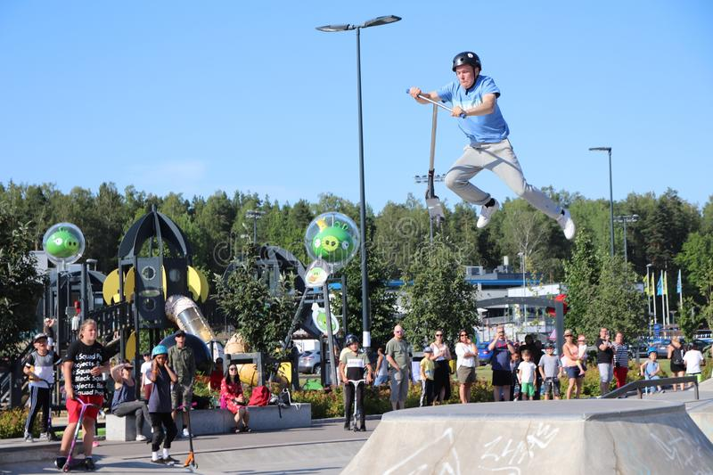 A competitor performing in Pro-series of Finnish Scooter Championships. FinScooter Summer Jam sport event was held in Leppaevaara skate park in Espoo, Finland royalty free stock photo